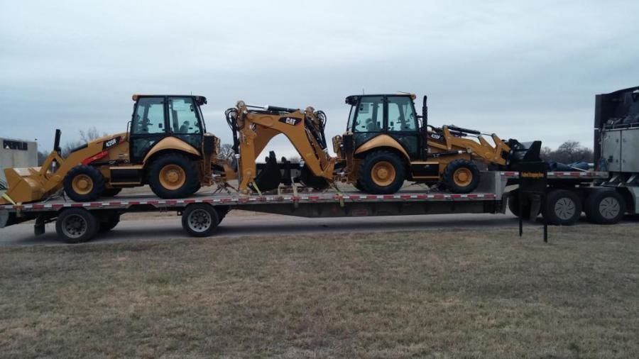 brand new Cat backhoes loaded on flatbed trailer