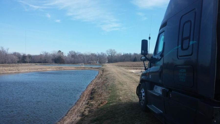 truck next to water on a narrow path