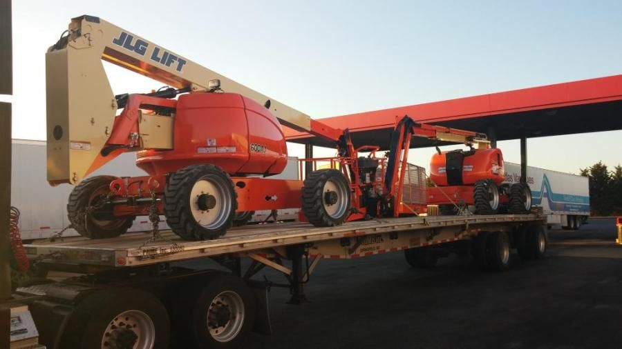 flatbed trailer loaded with jlg high lifts