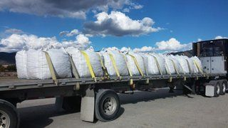 flatbed loaded and strapped with bags of rocks
