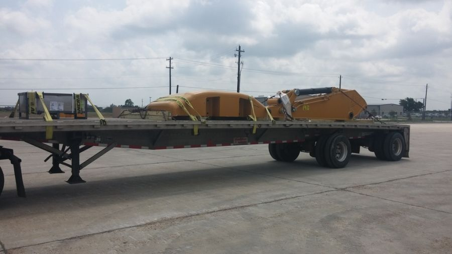 construction equipment counterweight strapped on a flatbed trailer being hauled from Texas to Washington