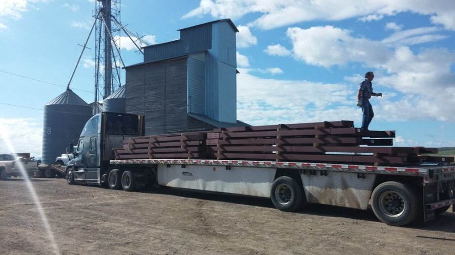 flatbed driver delivering pieces of a metal building to a farm in Idaho