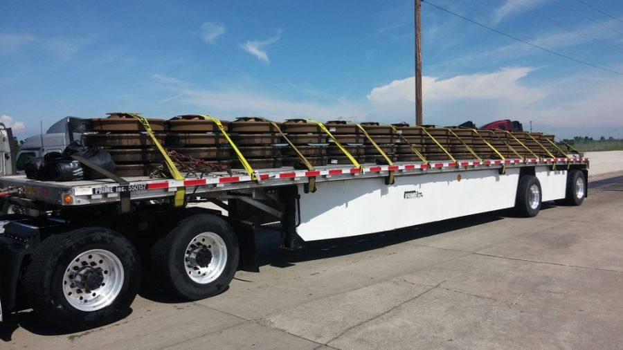 flatbed trailer with load of wheels for rail cars strapped to it
