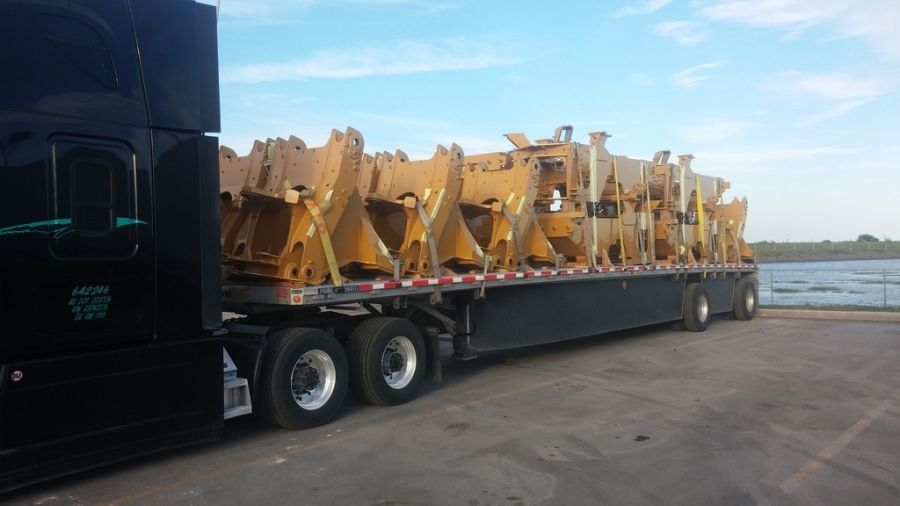 CAT parts loaded on flatbed trailer with skirts