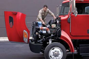 truck driver with hood up cooking on engine manifold