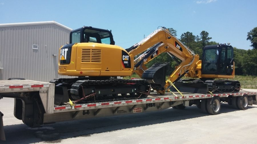yellow CAT mini-excavator loaded on flatbed trailer