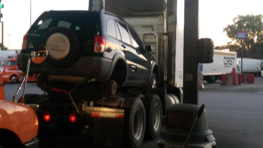 4-wheel SUV loaded and chained on a <span class=