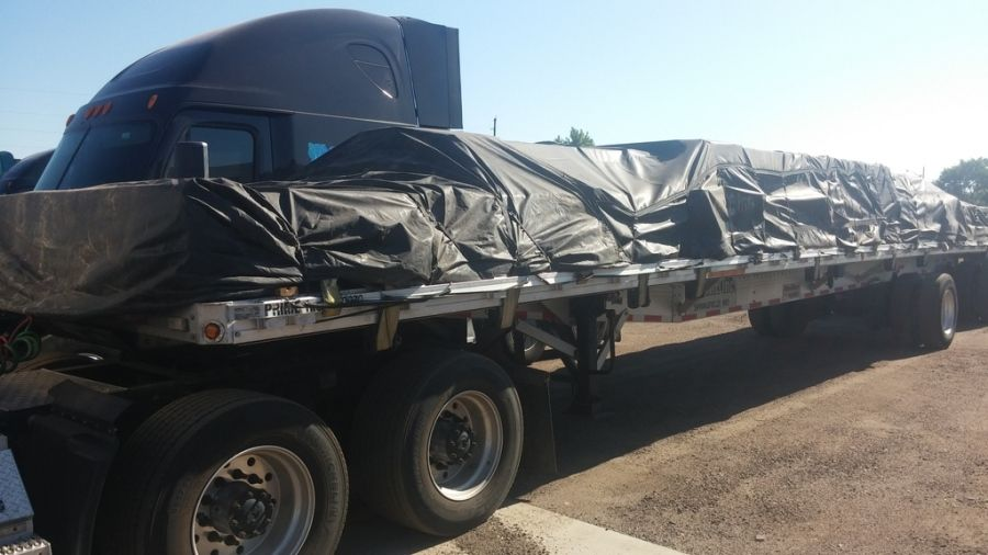 load of steel strapped tarped and secured on flatbed trailer