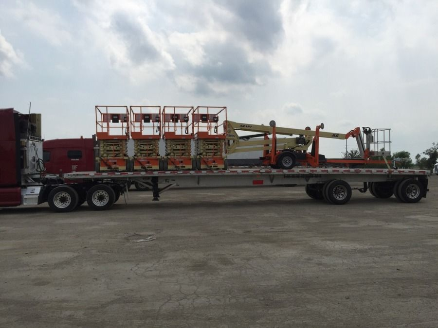 yellow high lift and orange scissor lifts loaded onto a flatbed trailer