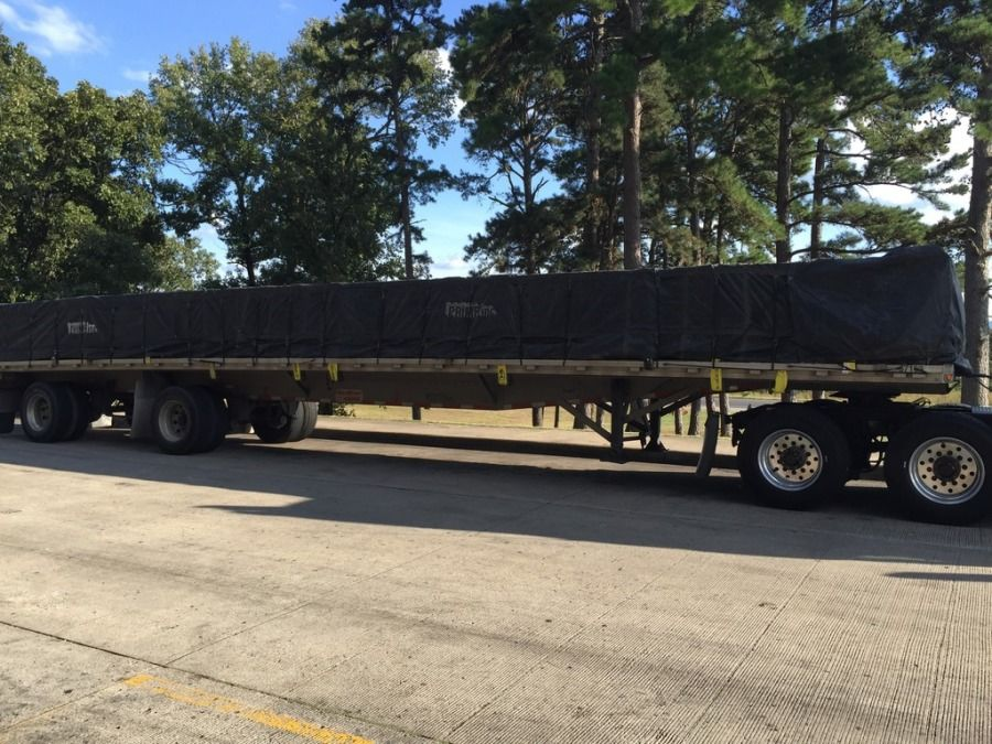 oversized load strapped and tarped on a flatbed trailer