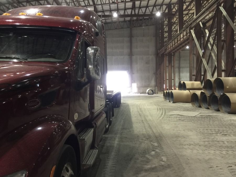 flatbed truck driver picking up inside slinky coil plant in Pueblo
