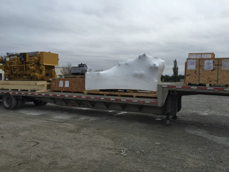 Caterpillar engine loaded on a flatbed trailer tarped and secured