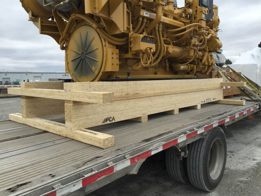 Caterpillar engine loaded on a flatbed trailer ready to be tarped and secured