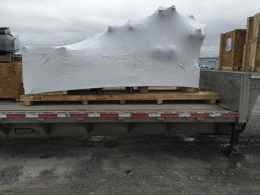 marine engine from Caterpillar loaded on a flatbed trailer tarped and secured