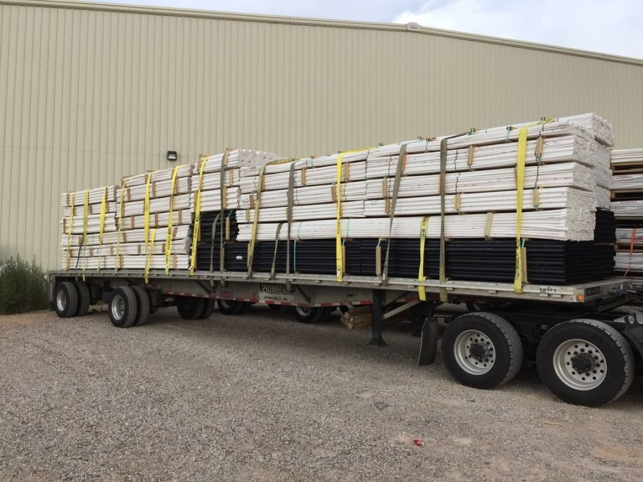 load of PVC pipe strapped and secured to flatbed trailer