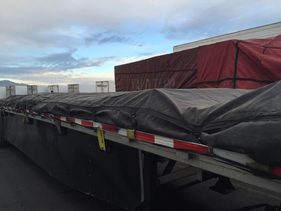 load of drywall and steel tarped and strapped on flatbed trailer headed to Missouri