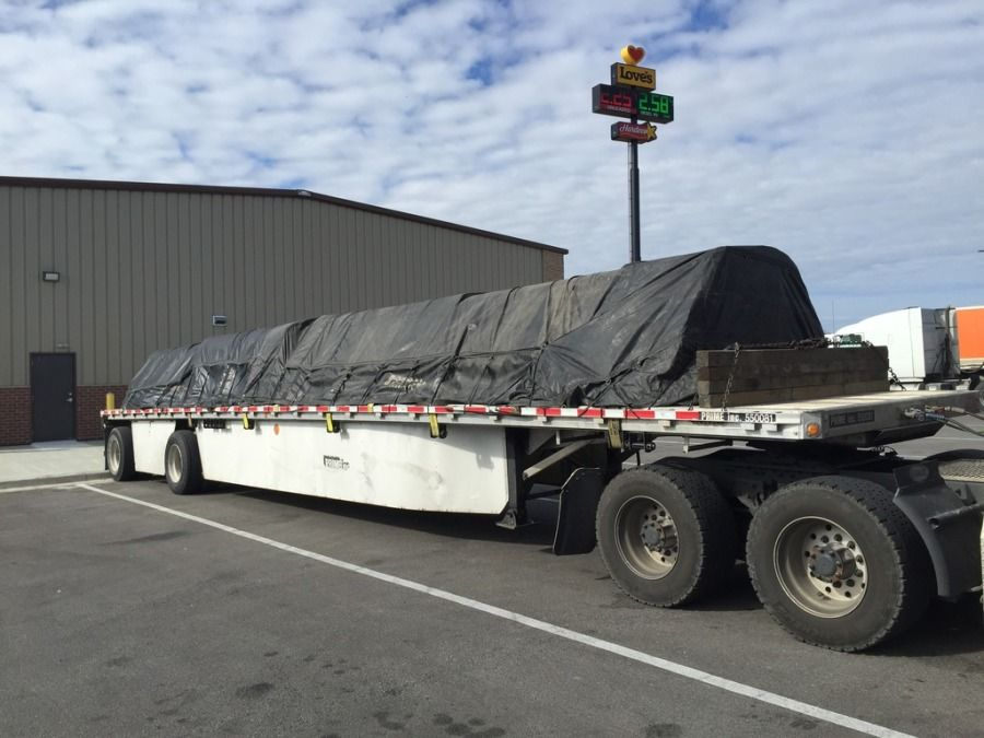 flatbed trailer loaded with small steel tubing tarped and strapped in Chicago