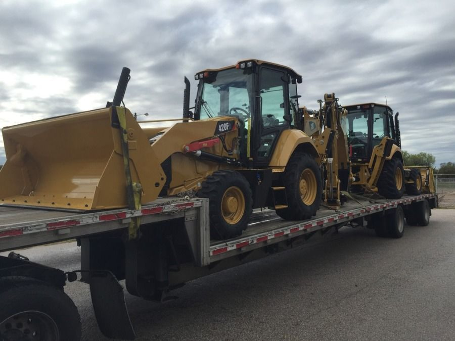 brand new yellow loaders from the factory loaded and chained on flatbed trailer