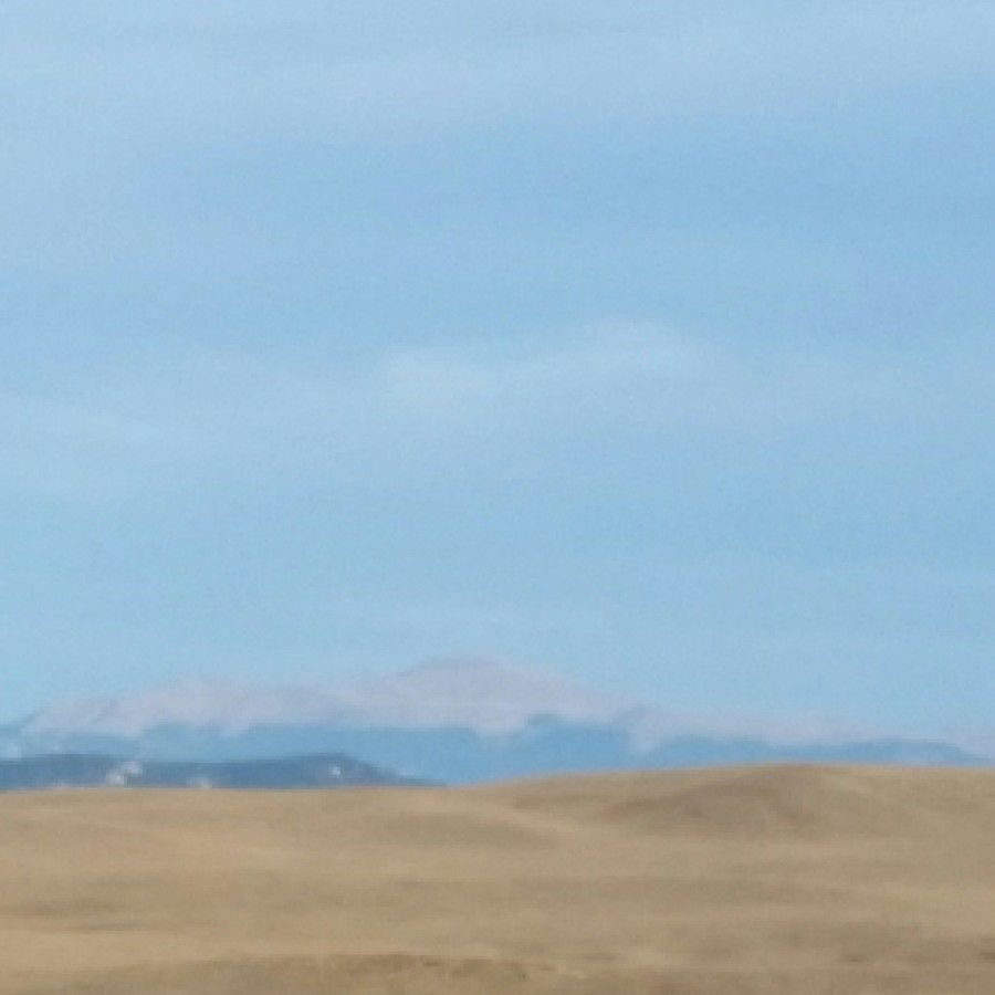 long-distance photo of the backside of Pike's Peak on a sunny day