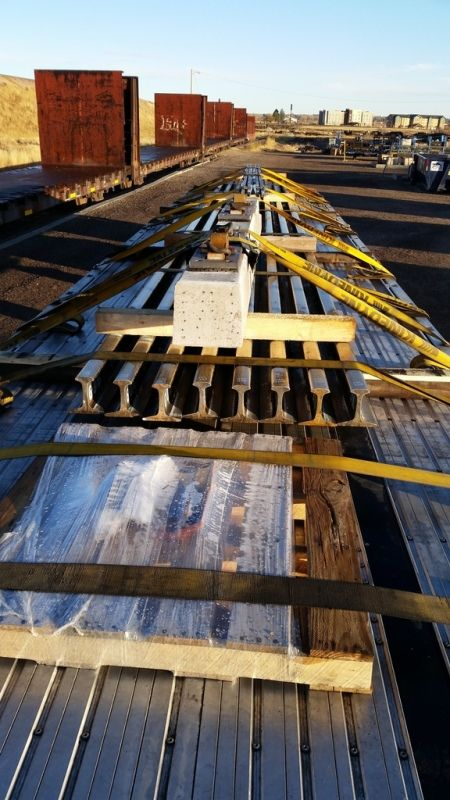 LTL flatbed trailer loaded and strapped with railroad ties and steel rails