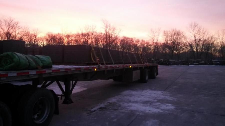 loaded strapped and tarped flatbed at sunrise