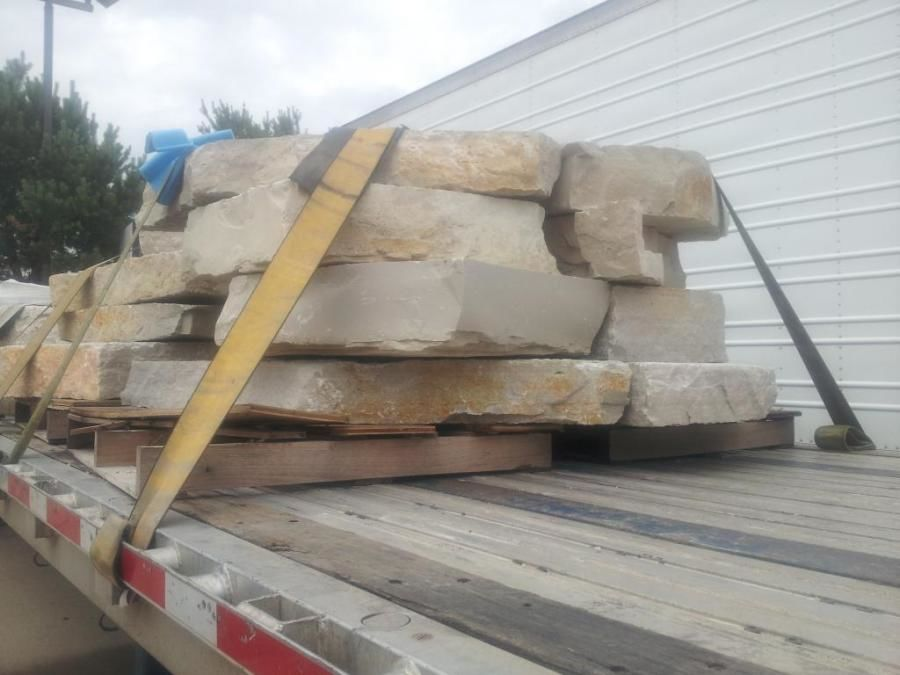 flatbed trailer with rock slabs strapped to it