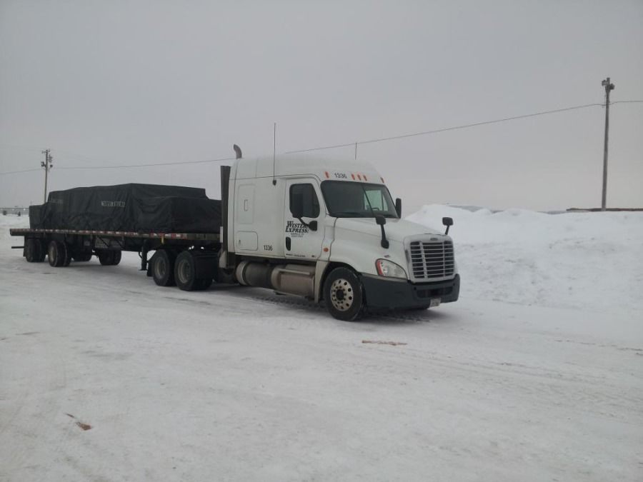 tarped flatbed truck in the snow in Otsego Michigan