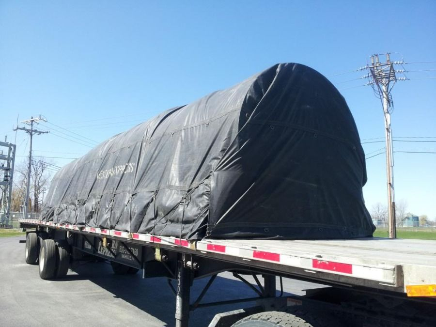 flatbed loaded with large paper rolls tarped and secured in Oakfield NY going to Danville PA