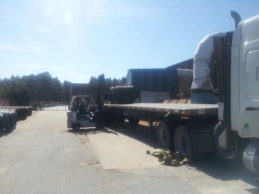 forklift loading metal slinky coils on flatbed trailer