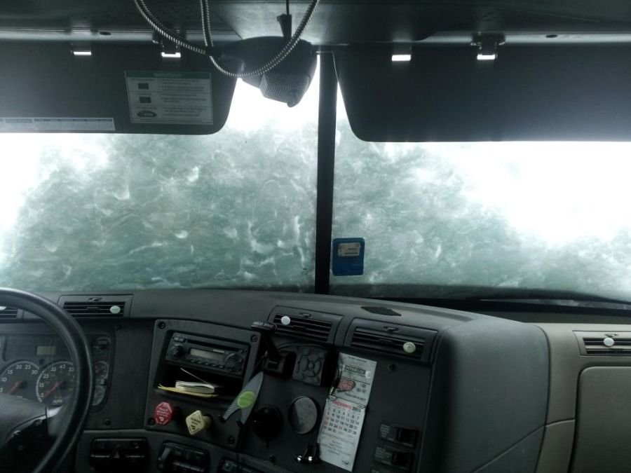 truck driver's view of a snow-covered windshield in the winter