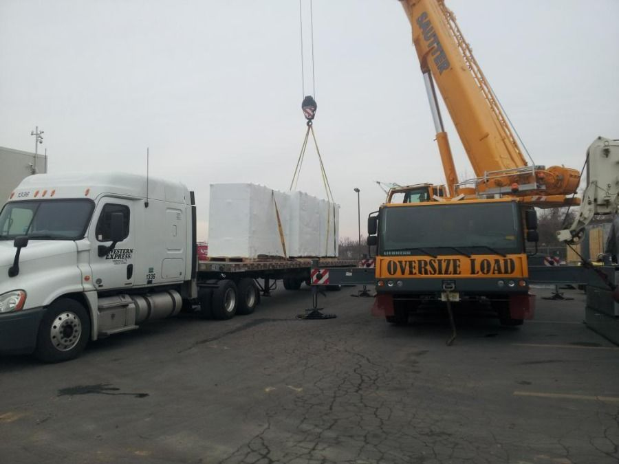 crane loading a flatbed trailer