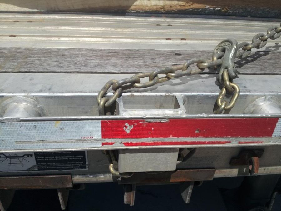 chain tear-dropped around stake pocket on flatbed trailer