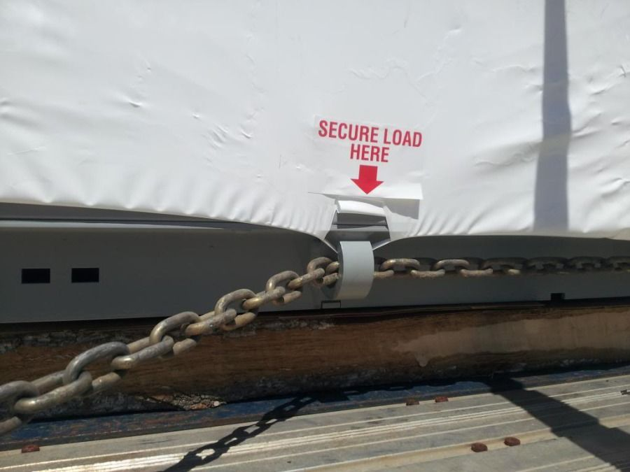 chain secured through steel rings on tarped flatbed trailer