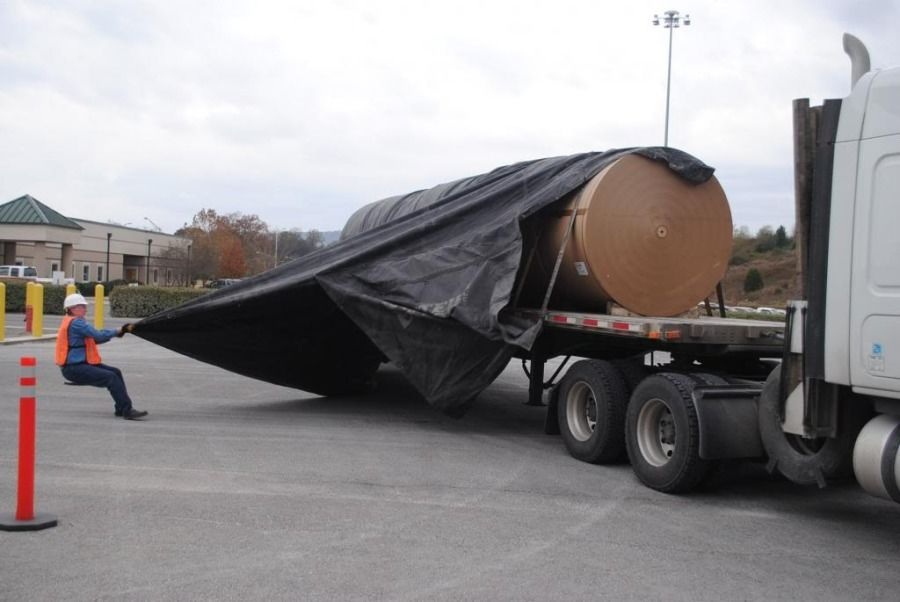 flat-bedder taking tarp off tank loaded on flatbed