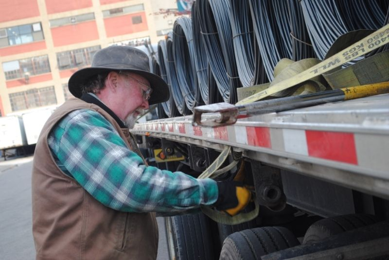 Truck driver strapping down metal coils on a flatbed