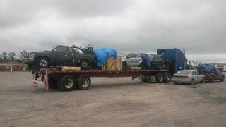 flatbed trailer loaded with car truck mattress and household goods