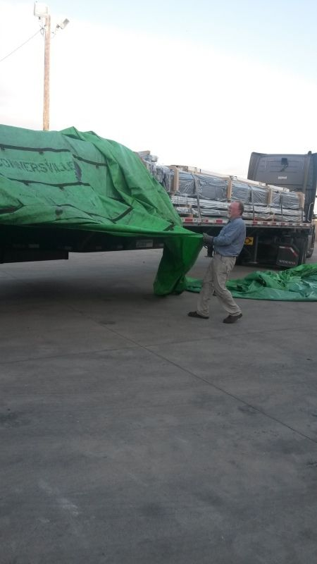 flatbedder removing tarps from a loaded flatbed trailer