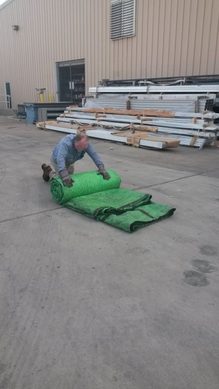 flatbedder removing rolling and storing tarps from a loaded flatbed trailer