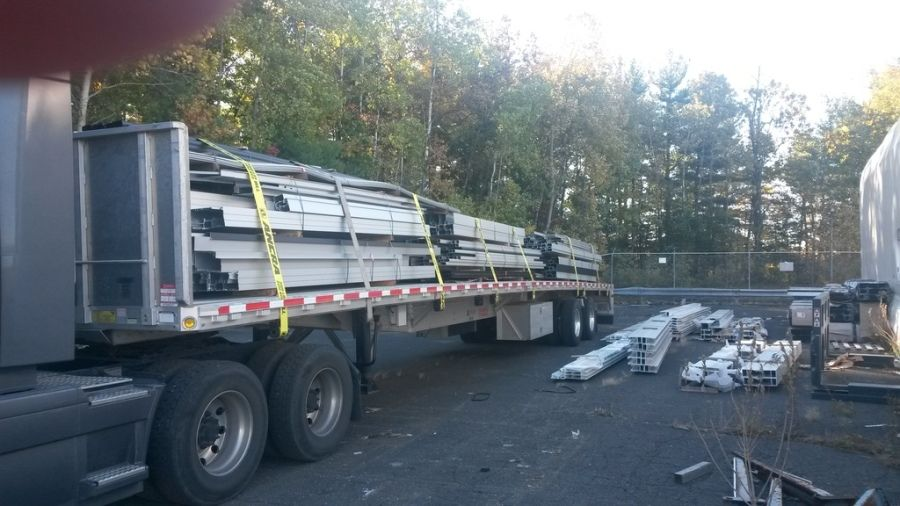 load of varied length steel beams strapped on to flatbed trailer
