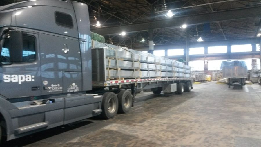 long joints of aluminum extrusions loaded and strapped on SAPA flatbed trailer in the warehouse
