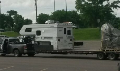 one-ton dually pulling a flatbed trailer with a camper loaded on it