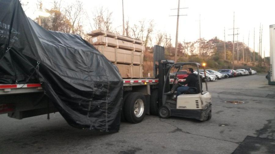 forklift driver unloading tarped flatbed in parking lot
