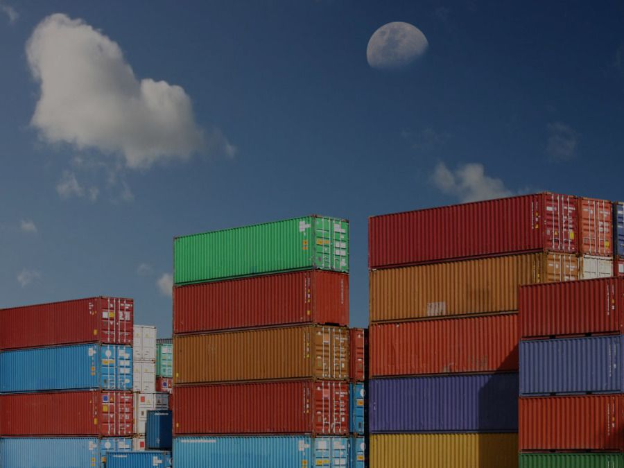 shipping containers stacked up at a port