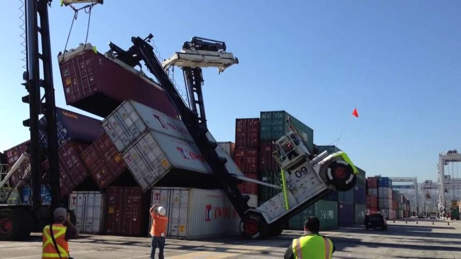 stacks of shipping containers knocked over at a port