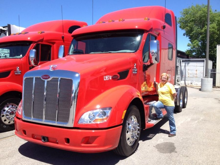 woman truck driver standing next to red Peterbilt truck