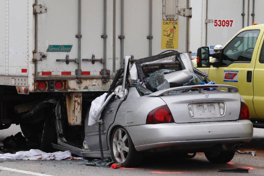 small car stuck under the 18-wheeler it crashed into at high speed killing the driver