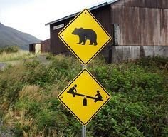 funny signs a bear crossing sign directly above children playing sign