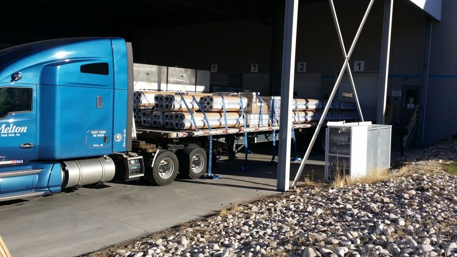 Melton flatbed loaded and strapped with hazmat glue tubes