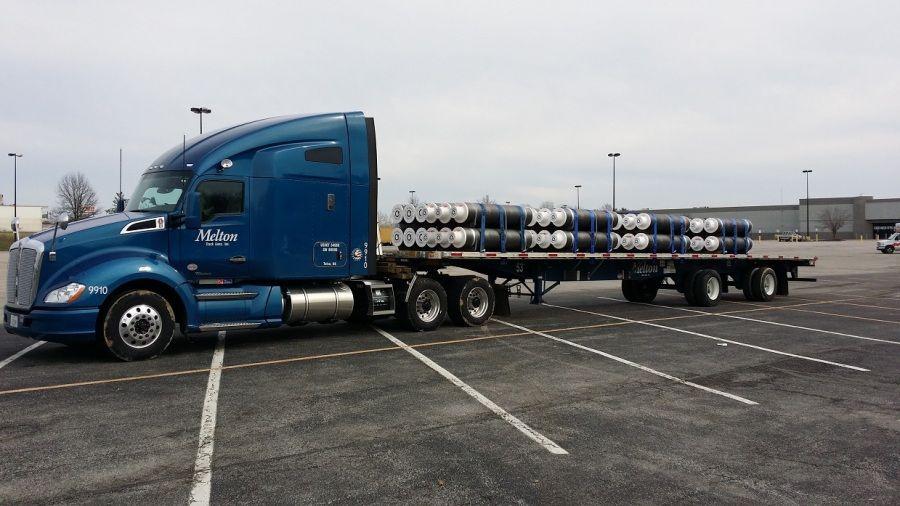 large steel tubes strapped on Melton flatbed trailer
