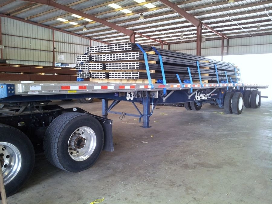 load of steel bars strapped on a flatbed trailer in a warehouse